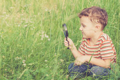 Happy little boy exploring nature with magnifying glass Stock Images