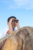 Happy little boy exploring outdoors clambering on a rock Royalty Free Stock Images