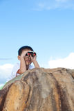 Happy little boy exploring outdoors clambering on a rock Royalty Free Stock Photos