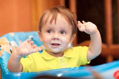 Happy little boy with face got dirty. Happy little boy wearing yellow t-shirt and looking aside smiles at home, face got dirty with yoghurt, he gesticulates royalty free stock photo