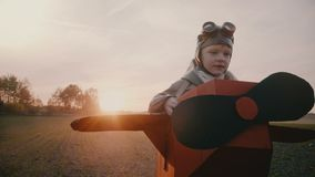 Happy little boy in fun cardboard plane costume running along a sunset autumn field playing aviation pilot slow motion. Smiling male child pretending to be an stock video footage