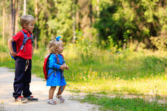 Happy little boy and girl with backpacks in summer Royalty Free Stock Photo