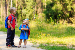 Happy little boy and girl with backpacks in summer Stock Photos