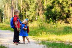 Happy little boy and girl with backpacks in summer Royalty Free Stock Images