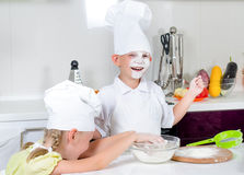Happy little boy and girl baking in the kitchen Stock Photos