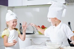 Happy little boy and girl baking in the kitchen Stock Photography