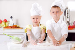 Happy little boy and girl cooking in the kitchen Royalty Free Stock Photos