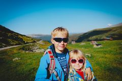 Happy little boy and girl hiking travel in nature. Family vacation stock photos
