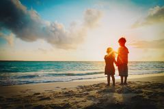 Happy little boy and girl holding hands at sunset royalty free stock photos