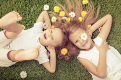 Happy little boy and girl lying on the grass Royalty Free Stock Images