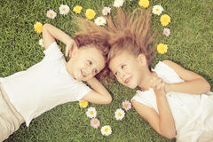 Happy little boy and girl lying on the grass Royalty Free Stock Image