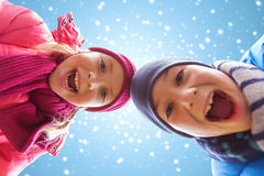Happy little boy and girl over blue sky with snow Royalty Free Stock Image
