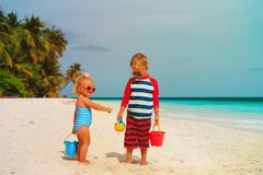 Happy little boy and girl play with sand on beach. Happy little boy and girl play with sand on tropical beach stock photography