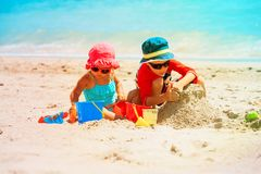 Happy little boy and girl play with sand on beach. Happy little boy and girl play with sand on tropical beach Royalty Free Stock Image