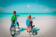 Happy little boy and girl ride bike on beach. Vacation stock images