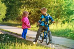 Happy little boy and girl riding bike in nature. Kids sport royalty free stock photos