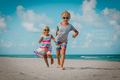Happy little boy and girl run play at beach royalty free stock photo