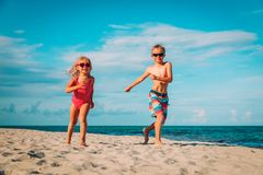 Happy little boy and girl run play at beach. Happy little boy and girl run play at tropical beach royalty free stock photography