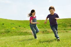 Happy little boy and girl running outdoors. Summer, childhood, leisure and people concept - happy little boy and girl playing tag game and running outdoors on Stock Images