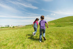 Happy little boy and girl running outdoors Royalty Free Stock Photos