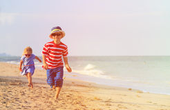 Happy little boy and girl running on sand beach Royalty Free Stock Photos