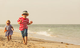 Happy little boy and girl running on sand beach Royalty Free Stock Image