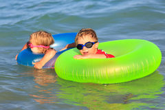 Happy little boy and girl swim at summer beach Royalty Free Stock Images