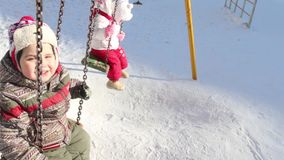 Happy little boy and girl swing at winter frost day stock footage