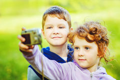 Happy little boy and girl taking self photo in the autumn park. royalty free stock image