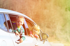 Happy little boy and girl travel by car in nature Stock Image