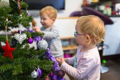 Boy and girl twins decorate Christmas tree. Happy little boy and girl twins decorate Christmas tree stock photos