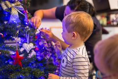 Boy and girl twins decorate Christmas tree. Happy little boy and girl twins decorate Christmas tree royalty free stock images
