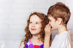 Happy Little boy and girl whispers in school. Stock Images