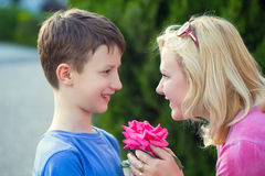 Happy little boy give flower to mom. Happy little caucasian boy give flower to mom, mother's day, outdoor Stock Image