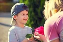 Happy little boy give flower to mom. Vintage, mother's day, motherhood Stock Images