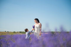 Happy little boy giving bouquet of flowers to mother standing among blooming field Stock Photography