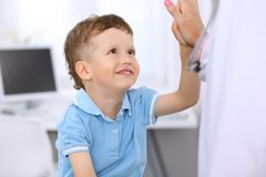Happy little boy giving high five after health exam at doctor`s office.  stock photos