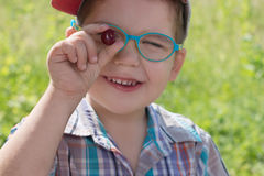 Happy little boy in glasses holds cherry at summer day outd. Happy little cute boy in glasses holds cherry at summer day outdoor, focus on berry Royalty Free Stock Photo