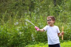 Happy little boy in glasses plays with soap bubbles. In green forest Royalty Free Stock Photos