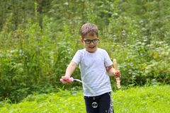 Happy little boy in glasses plays with soap bubbles. In summer green forest Royalty Free Stock Photography