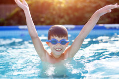 Happy little boy in goggles enjoying play in pool. Hurray, summer holiday Stock Image