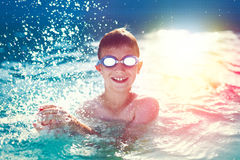 Happy little boy with goggles splashing in swimming pool Royalty Free Stock Photos