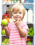 Happy little boy with green apple showing his Stock Image