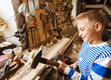 Happy little boy with hammer and plank at workshop Stock Photos
