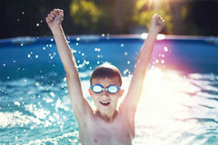 Happy little boy hands up in swimming pool in sunset Royalty Free Stock Image