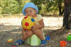 Happy little boy in the hat sits on a child's potty. Stock Photos