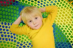 Happy little boy having fun in amusement in play center. Child playing on indoor playground royalty free stock images