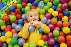 Happy little boy having fun in ball pit with colorful balls. Child playing on indoor playground stock photography
