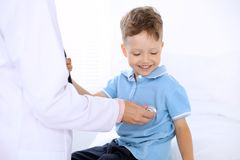 Happy little boy having fun while is being examine by doctor by stethoscope. Health care, insurance and help concept.  Royalty Free Stock Image