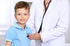 Happy little boy having fun while is being examine by doctor by stethoscope. Health care, insurance and help concept Royalty Free Stock Image